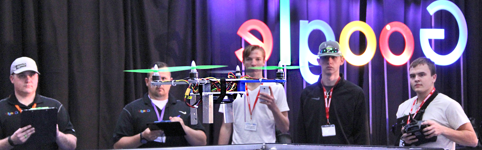 Boy flying drone with team and judges watching