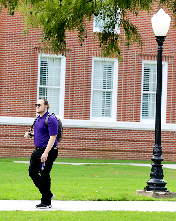 Boy walking across campus