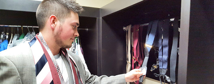 Student trying on suit and ties from coat closet
